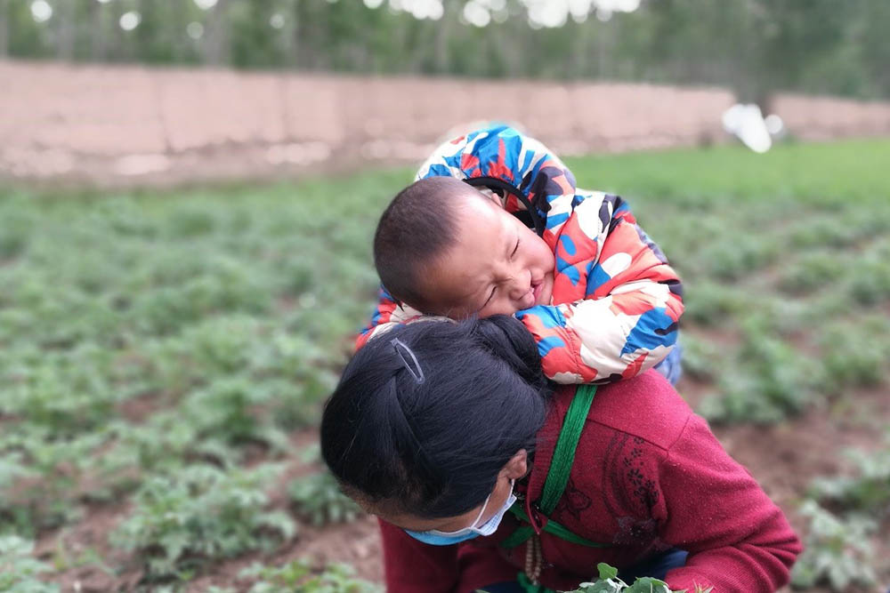 Bao strapped to his mother's back while she works on the farm
