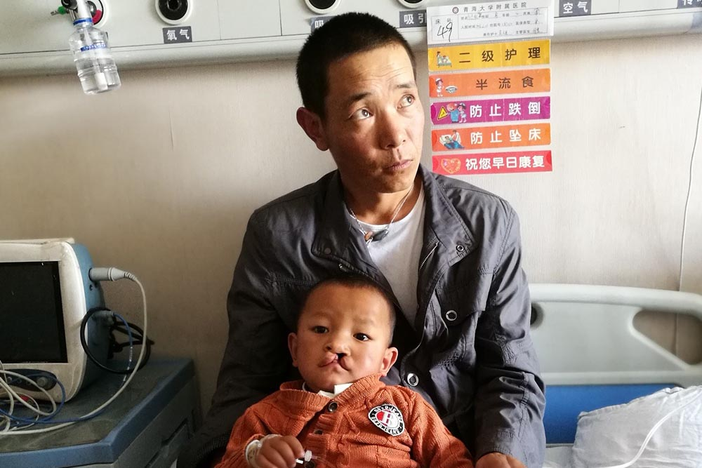 Bao lays on his father's lap in a hospital bed