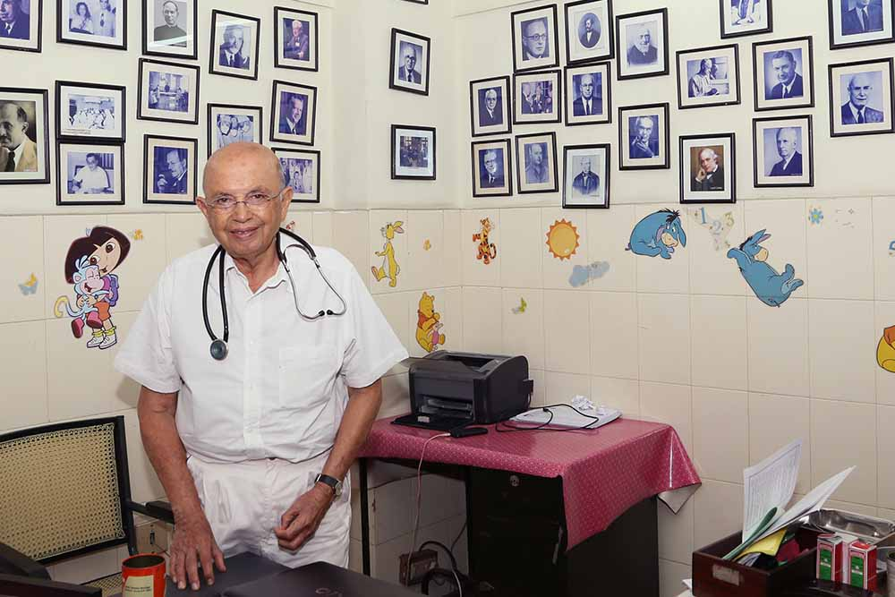 Dr Adenwalla in his office full of images of surgeons