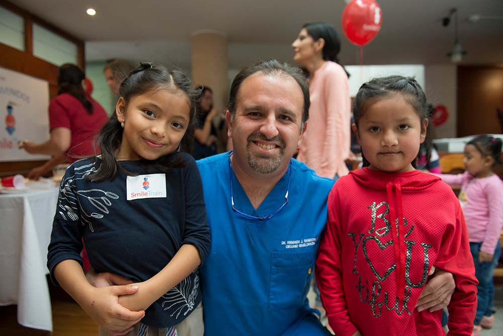 Dr Sandoval Jr with two cleft patients