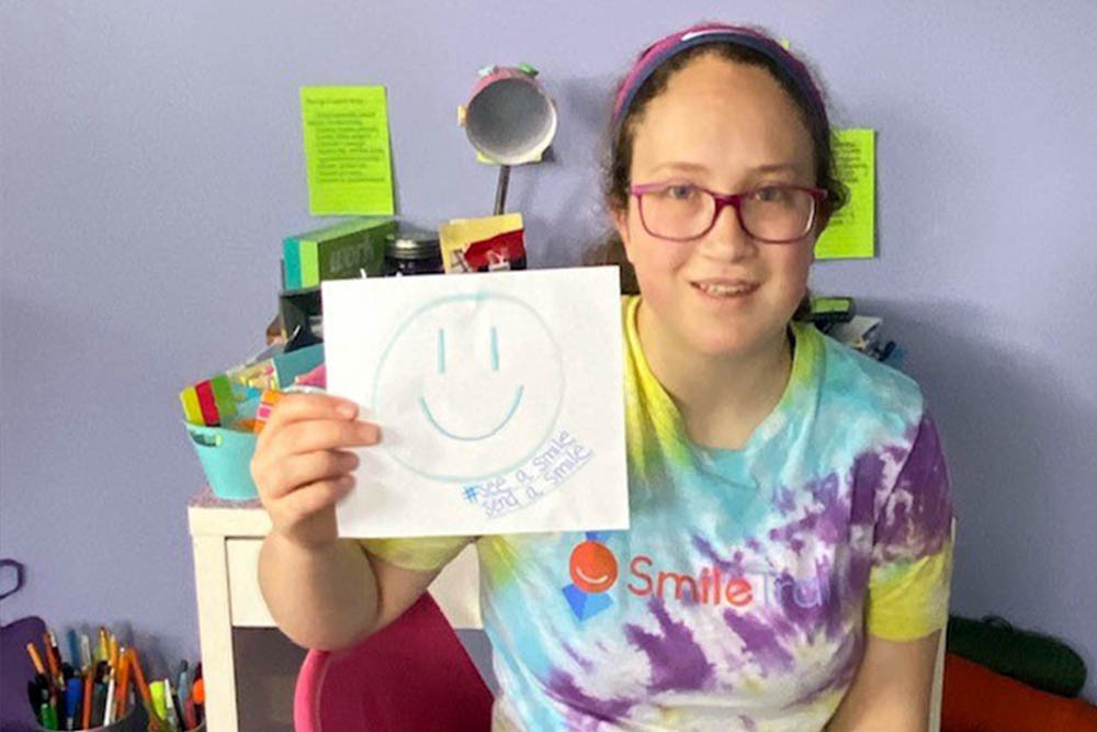 Grace holds up Smile Train social media sign