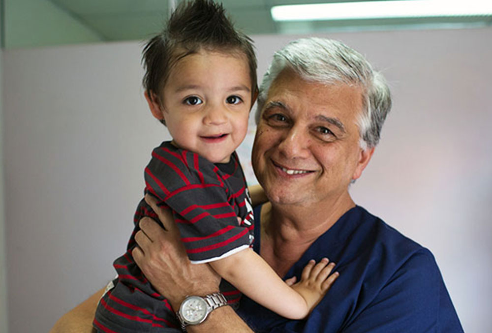 Smile Train partner surgeon holding a child with a cleft lip and palate after surgery