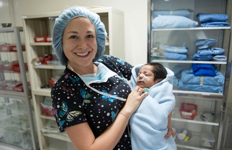 Doctor holds baby after cleft surgery