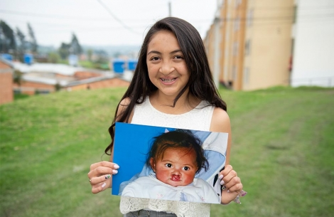 Monica holding an image of herself as a child