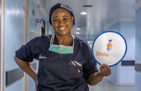 Cleft surgeon from Nigeria holding Smile Train sign