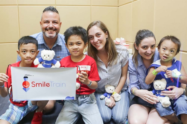 group of smile train supporters poses with patients in Asia
