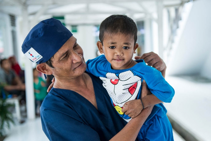 A Smile Train surgeon from Indonesia lifts a patient