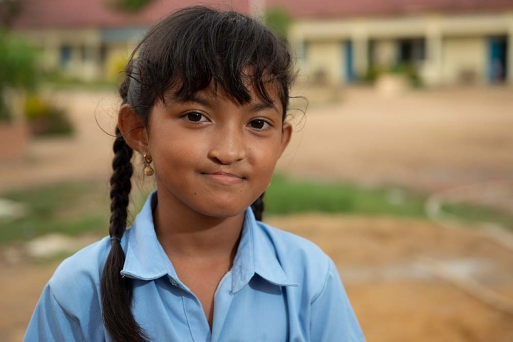 Samnang smiles in front of her school