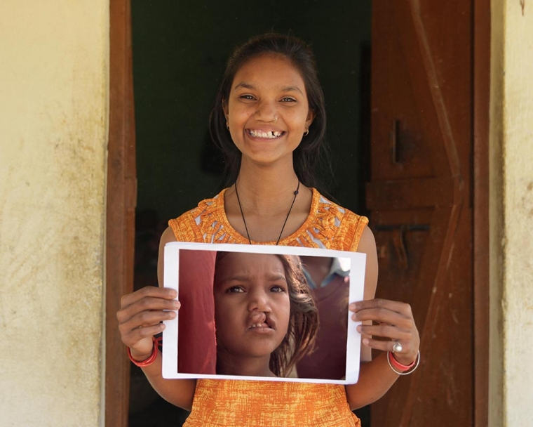 Pinki holds image of herself from documentary film Smile Pinki