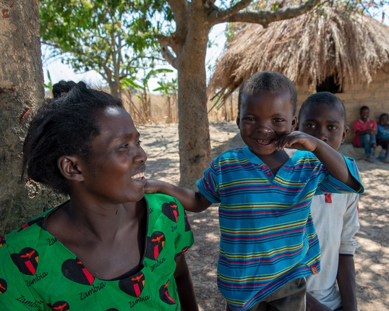 Oscar with his mother outside in their village in Zambia after his free Smile Train-sponsored cleft treatment.